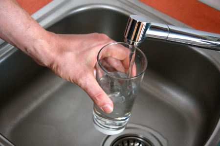 drinkable: Pouring tap water by man s hand