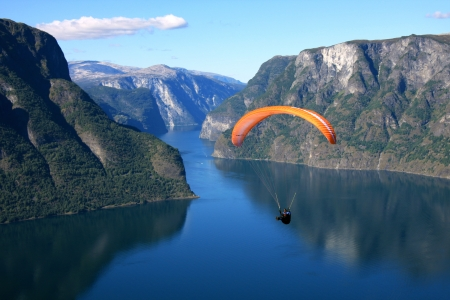 paragliding: Paraglider flies through the Norwegian fjord Editorial