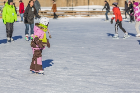 A young child is learning with joy how to ice skate in a really cold winter day in the Skating Rink in Old Port of Montreal, Quebec, Canada