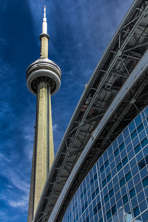 The CN Tower on a blue sky background in beautiful day. Its location is in Toronto, Canada.