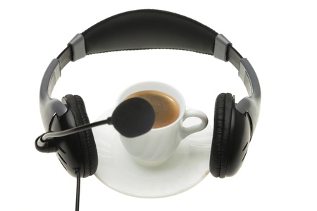 Headphones with a microphone, over cup coffee, isolated on the white background, concepts for coffee-music time. photo