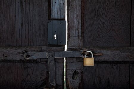 closed black wooden door with a padlock, front photo