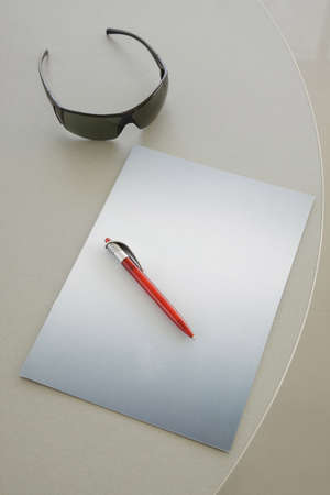 Red Pen on a grey notebook and glasses photo