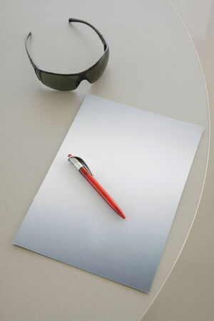 red pen: Red Pen on a grey notebook and glasses Stock Photo