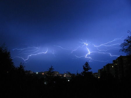 bad weather: Beautiful powerful lightning over city, zipper and thunderstorm, dark sky with bright electrical flash, thunder and thunderbolt, bad weather concept Stock Photo