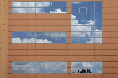 reflecting: Clouds lit by the setting sun reflecting in a modern office building windows