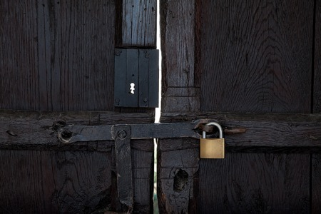closed black wooden door with a padlock, front