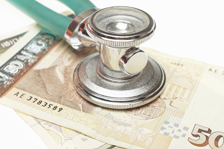 high cost: Stethoscope on the top of the money. Selective focus on stethoscope. It could describe high cost of medicine or bribe in medicine. Stock Photo