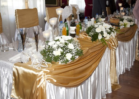 arranging chairs: catering table set service with silverware, fresh flowers and glass at restaurant before party