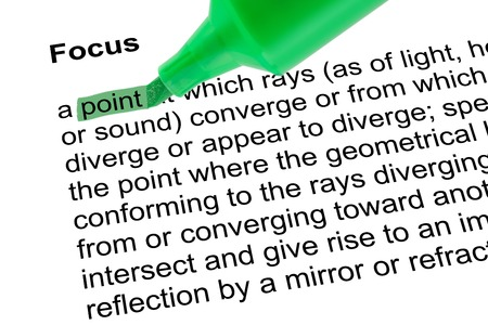 prominence: Highlighted word point for Focus with green pen over white paper. Isolated white background.