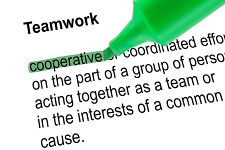 Highlighted word cooperative for Teamwork with green pen over white paper. Isolated white background. Stock Photo