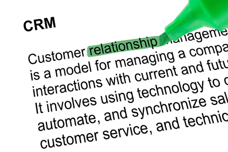 definition define: Highlighted word relationship for CRM with green pen over white paper. Isolated white background.