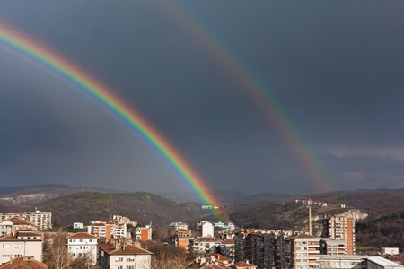 sity: beautiful double full rainbow in blue sky after the rain over sity Stock Photo