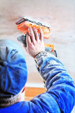 concrete surface finishing: Master smooth gypsum plaster and grinding on the wall in an unfinished house