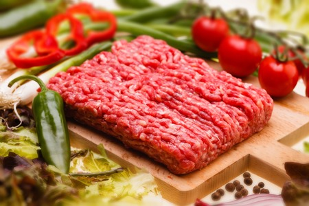 farce: raw minced meat with vegetables on wooden board, selective focus Stock Photo
