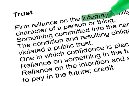 relevance: Highlighted word integrity for Trust with green pen over white paper. Isolated white background.
