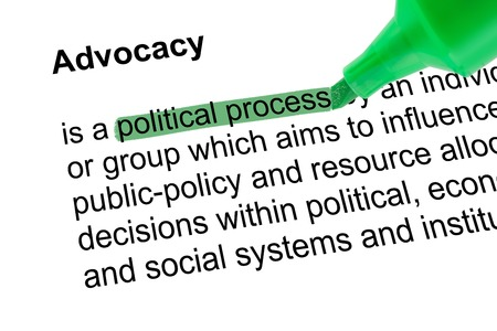 lexicographer: Highlighted words  political process for Advocacy with green pen over white paper. Isolated white background.