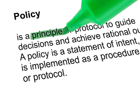 lexicographer: Highlighted word principle for Policy with green pen over white paper. Isolated white background.