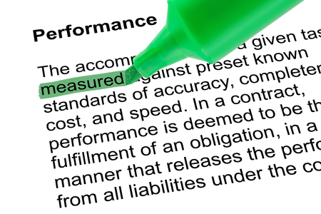lexicographer: Highlighted word measured for Performance with green pen over white paper. Isolated white background.