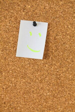 pin board: White note with a smile  pinned on the textured pin board
