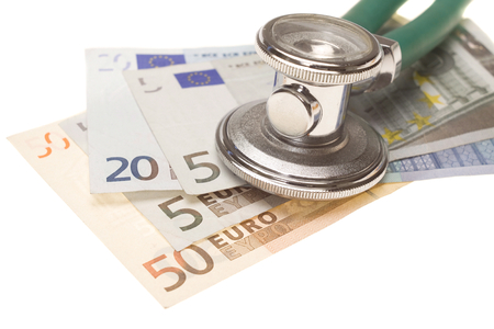 describe: Stethoscope on the top of the money. Selective focus on stethoscope. It could describe high cost of medicine or bribe in medicine. Stock Photo