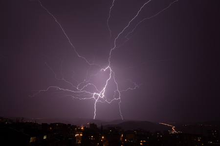 thundershower: Beautiful powerful lightning over city, zipper and thunderstorm, dark sky with bright electrical flash, thunder and thunderbolt, bad weather concept Stock Photo