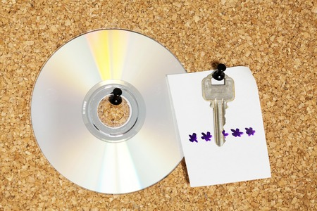 dvd rom: idea for key with note for password of CD over cork background Stock Photo
