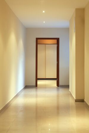 house walls: long and beautiful corridor with open door in a modern hotel, front Stock Photo