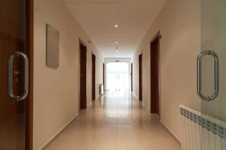 long and beautiful corridor with open door in a modern hotel, front Stock Photo