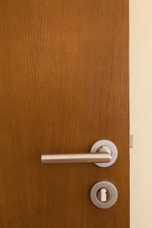 Moderne stijl deurgreep op natuurlijke houten deur *** Local Caption *** ????? ?????? ???