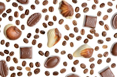 cafe bombon: Surtido de dulces de chocolate en el fondo de los granos de café aislados Foto de archivo