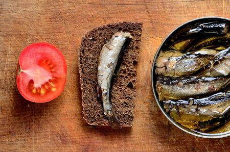 sprat: sandwich with sprats, sliced tomatoes and a can of sprats on an old cutting board