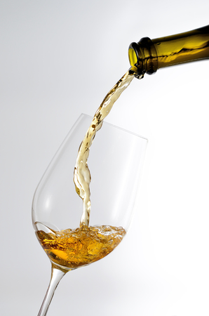 White wine pouring in a glass from a bottle Stock Photo