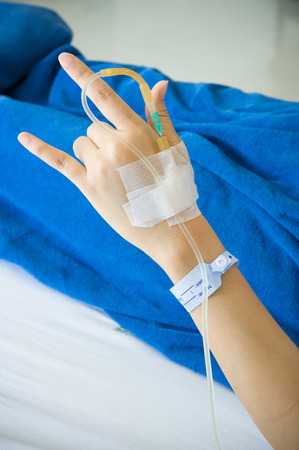 recieving: Female patients hand recieving iv saline solution in hostpital. shoot on white bed background