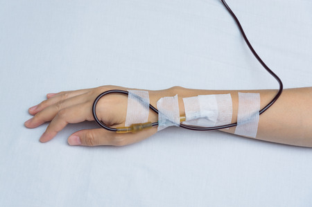 transfusion: Patients arm show blood transfusion in hostpital. shoot on white bed background