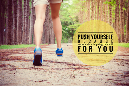 Inspirational quote on legs running through pine tree forest trail,