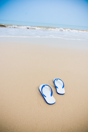swim shoes: White sandals with blue stripe left on beachside.