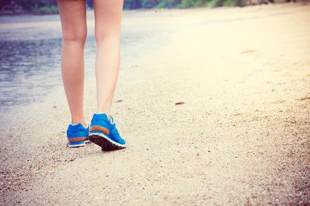 女性の脚を実行しているまたは、ビーチに沿って歩きます。 写真素材