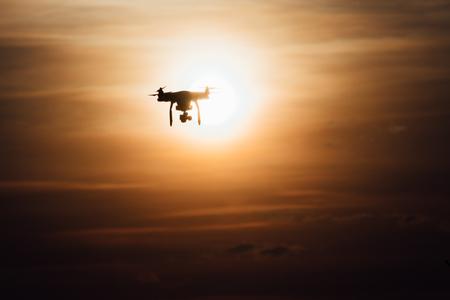 Siloutte シーンでの暖かい色の夕日飛ぶ無人機