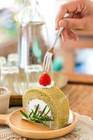 Hand holding wooden plate of matcha green tea cake with fork, rosemarry over vintage table cloths.