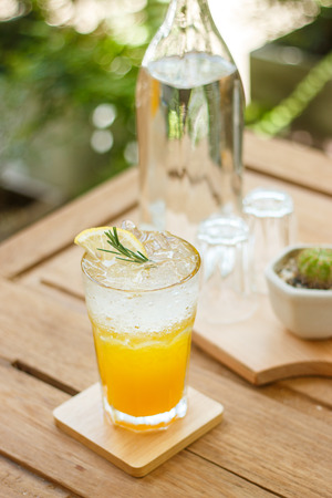 Orange soda drinks in tropical tree show wooden table and plate in nice atmosphere.