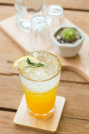 熱帯の木でオレンジ ソーダ飲料は、素敵な雰囲気の木製のテーブルとプレートを表示します。