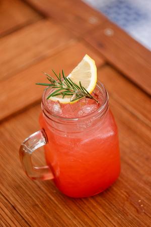 ストロベリー ソーダ飲料熱帯の木では、素敵な雰囲気の中で木製のテーブルとプレートを表示します。