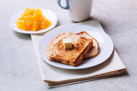 白い皿にバターを溶かし、オレンジ色のフルーツをセラミックグラスで焼きます。
