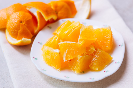 Orange sliced in lovely white plate with rose pattern over clean natural cloths decored with orange peel. Standard-Bild