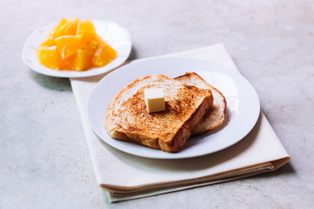 Toast bread on white plate with butter melting on and some orange fruit beside with ceramic glass. Standard-Bild