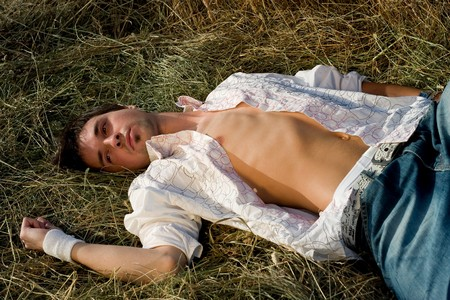 Young Man with chest relaxing on the hay photo