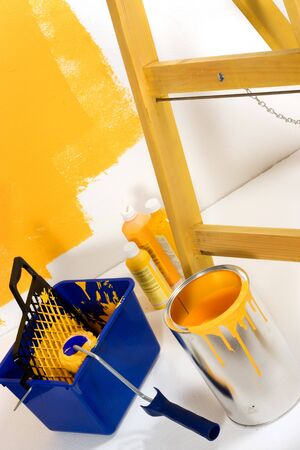 Yellow painting with ladder, roller brush, bucket and yellow pigments