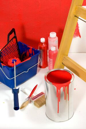 Red painting with ladder, roller brush, bucket and red pigments Stock Photo