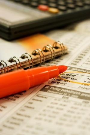 Orange highlighter, calculator lying on a bursa charts photo